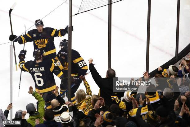 Kevan Miller of the Boston Bruins celebrates with Colin Miller and Jimmy Hayes after scoring against the Vancouver Canucks during the first period...