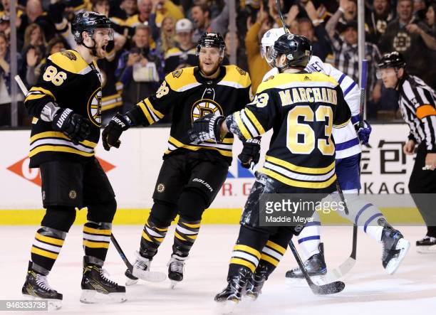 Kevan Miller of the Boston Bruins celebrates with David Pastrnak and Brad Marchand after scoring a goal against the Toronto Maple Leafs during the...