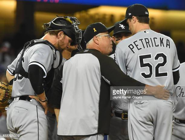 Kevan Smith of the Chicago White Sox looks on as manager Rick Renteria talks with pitcher Jake Petricka during the game against the Los Angeles...
