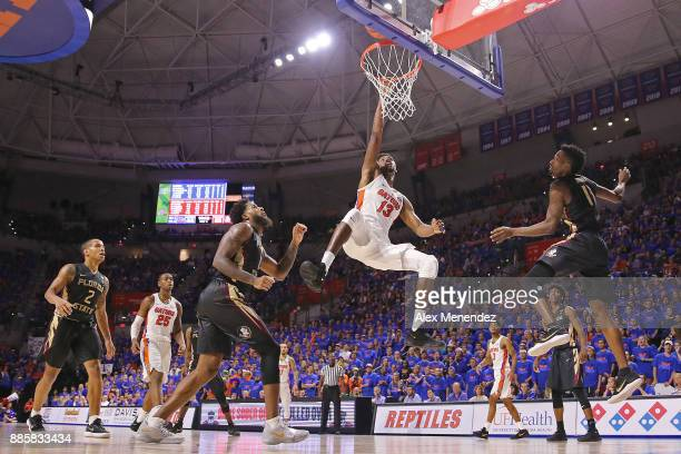 Kevarrius Hayes of the Florida Gators attempts a shot in front of Phil Cofer and Braian Angola of the Florida State Seminoles during a NCAA...