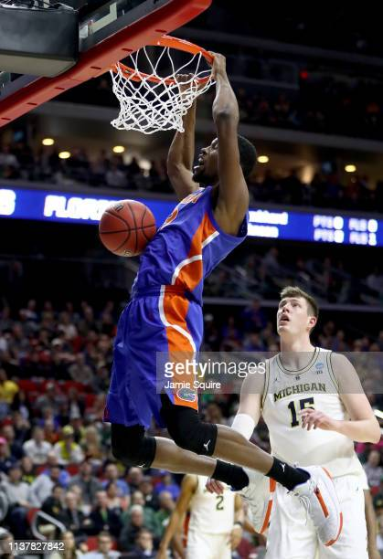 Kevarrius Hayes of the Florida Gators dunks the ball against Jon Teske of the Michigan Wolverines during the first half in the second round game of...