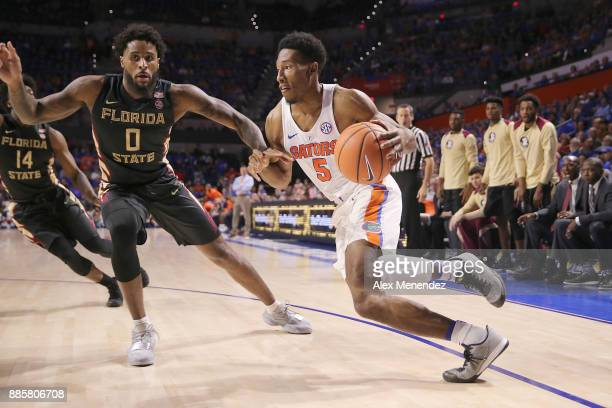 KeVaughn Allen of the Florida Gators dribbles to the basket in front of Phil Cofer of the Florida State Seminoles during a NCAA basketball at the...