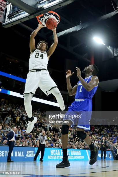 Keve Aluma of the Wofford Terriers dunks the ball over Michael Nzei of the Seton Hall Pirates in the first half during the first round of the 2019...