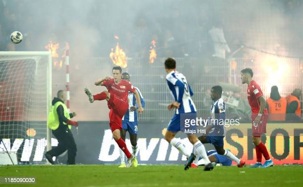 Keven Schlotterbeck of 1 FC Union Berlin clears the ball as fans set alight to clothing during the Bundesliga match between 1 FC Union Berlin and...