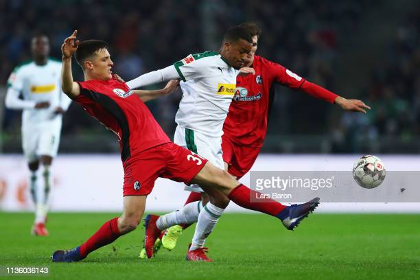Keven Schlotterbeck of SC Freiburg tackles Alassane Plea of Borussia Monchengladbach during the Bundesliga match between Borussia Moenchengladbach...