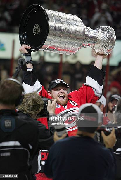 Kevin Adams of the Carolina Hurricanes hoists the Stanley Cup in front of media cameras after the Hurricanes defeated the Edmonton Oilers in game...