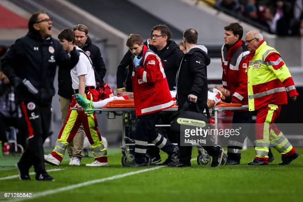 Kevin Akpoguma of Duesseldorf is carried injured off the field during the Second Bundesliga match between Fortuna Duesseldorf and FC St Pauli at...