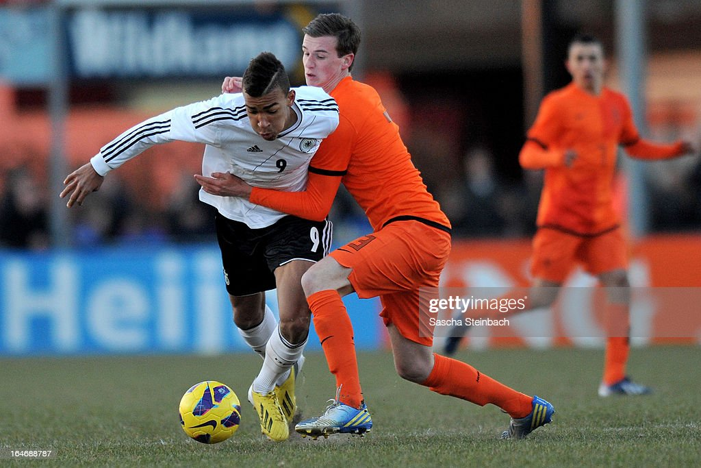 Kevin Akpoguma of Germany (L) is tackled by Peet Bijen of The Netherlands (R) during the U18 International Friendly match between The Netherlands and Germany on March 26, 2013 in Vriezenveen, Netherlands.