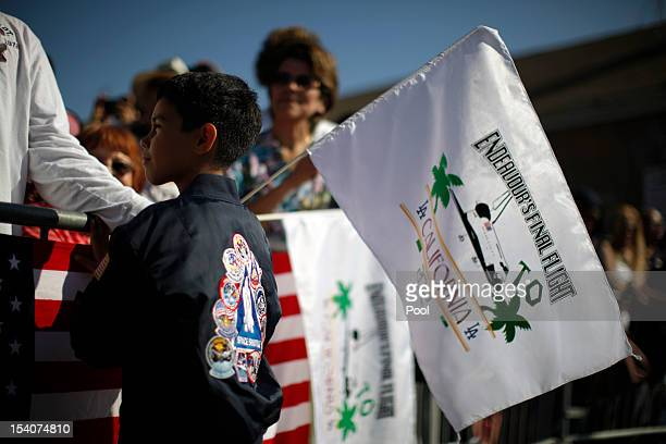 Kevin Alcaraz waves a flag as the Space Shuttle Endeavour is moved to the California Science Center on October 13 2012 in Inglewood California The...