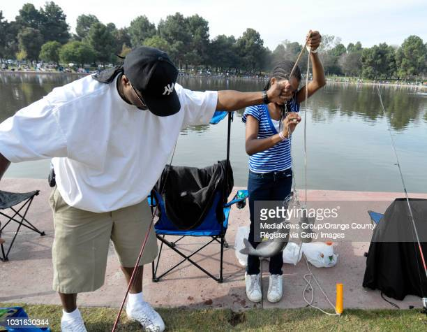 BEACH CA Kevin Allen helps his daughter Mariana Allen take care of the fish she caught during the Annual Youth Fishing Derby at El Dorado Regional in...
