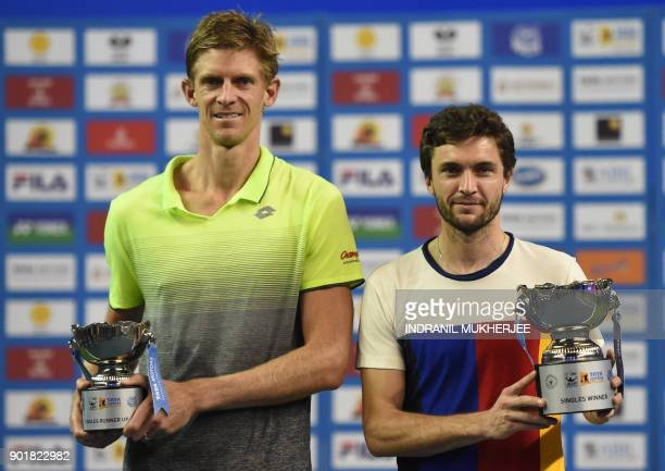 Kevin Anderson of South Africa and Gilles Simon of France pose with the men's single runnerup and winners trophy of the Tata Open Maharashtra ATP...