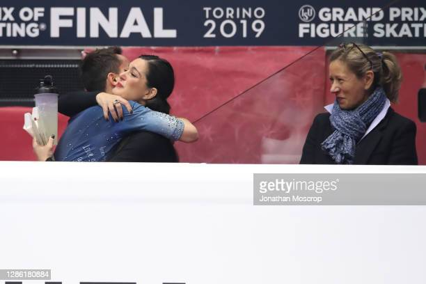 Kevin Aymoz of France is embraced by his Italian coach Silvia Fontana, whilst Katia Krier looks on following his performance in the Men's Free...