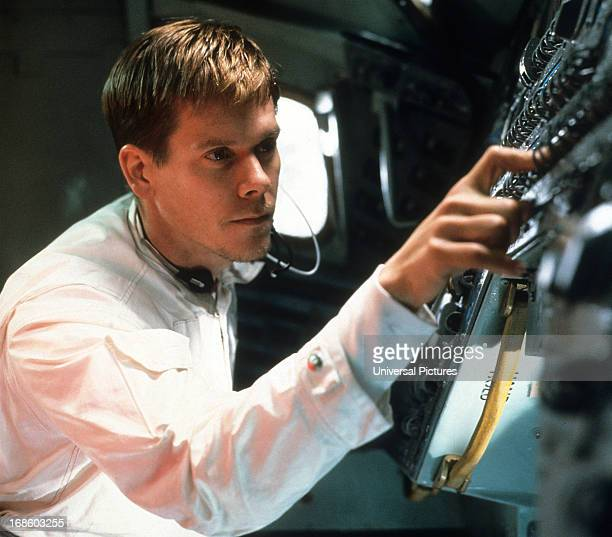 Kevin Bacon checking controls in a scene from the film 'Apollo 13' 1995