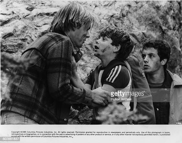 Kevin Bacon is grabbed by Sean Astin as KC Martel looks on in a scene of the 'White Water Summer' circa 1987