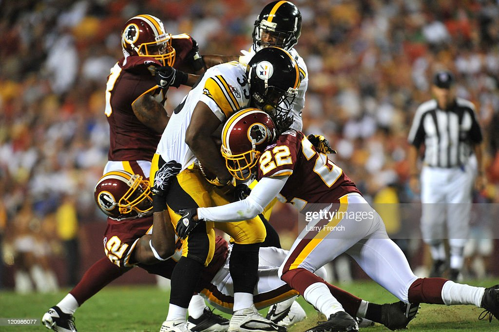 Kevin Barnes #22 of the Washington Redskins tackles Isaac Redman #33 of the Pittsburgh Steelers at FedExField on August 12, 2011 in Landover, Maryland. The Redskins defeated the Steelers 16-7.