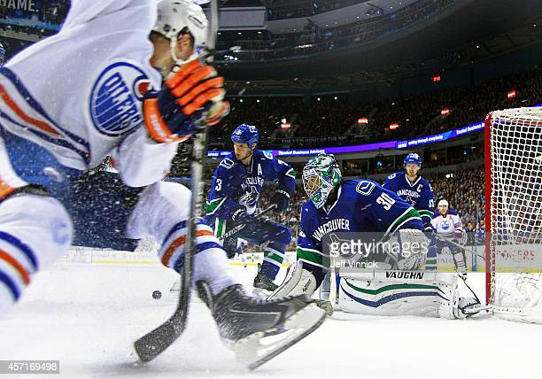 Kevin Bieksa and Ryan Miller of the Vancouver Canucks watch the rebound off the shot of Taylor Hall of the Edmonton Oilers during their NHL game at...
