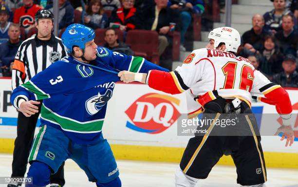 Kevin Bieksa of the Vancouver Canucks and Tom Kostopoulos of the Calgary Flames trade punches three seconds into the NHL game at Rogers Arena...