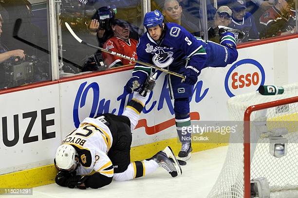 Kevin Bieksa of the Vancouver Canucks checks Johnny Boychuk of the Boston Bruins into the boards during game one of the 2011 NHL Stanley Cup Finals...