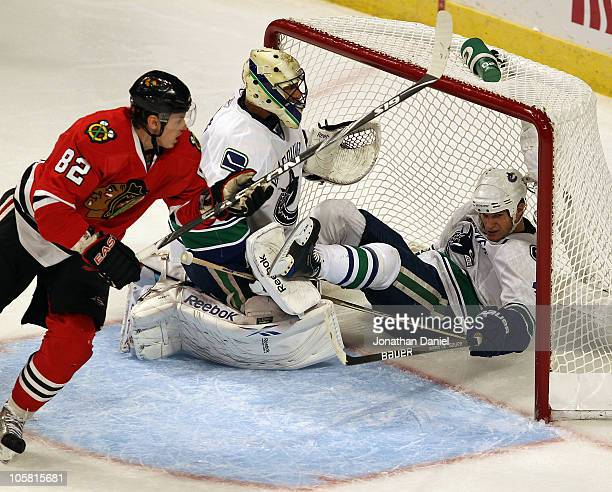 Kevin Bieksa of the Vancouver Canucks falls over Roberto Luongo on an interference call against Tomas Kopecky of the Chicago Blackhawks at the United...