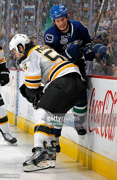 Kevin Bieksa of the Vancouver Canucks gets checked by Adam McQuaid of the Boston Bruins in Game Two of the 2011 NHL Stanley Cup Finals at Rogers...