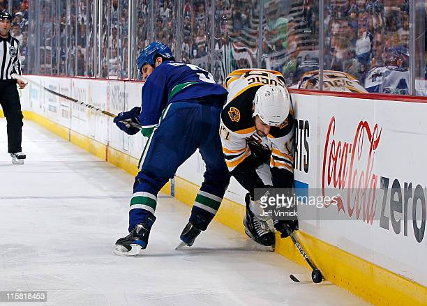 Kevin Bieksa of the Vancouver Canucks hip checks Milan Lucic of the Boston Bruins into the boards during Game Five of the 2011 NHL Stanley Cup Finals...