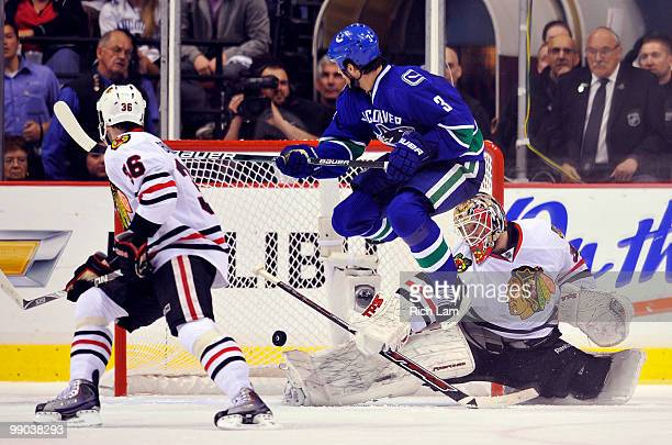 Kevin Bieksa of the Vancouver Canucks jumps out of shot while goalie Antti Niemi of the Chicago Blackhawks makes a save as Dave Bolland of the...