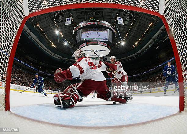Kevin Bieksa of the Vancouver Canucks scores a goal on Ilya Bryzgalov of the Phoenix Coyotes while teammate Ed Jovanovski looks on during their game...