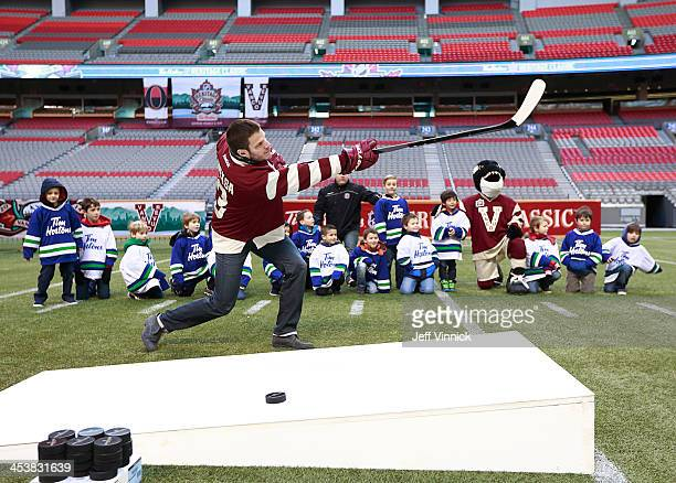 Kevin Bieksa of the Vancouver Canucks shoots a puck 70 yards through the football goal posts at BC Place during a media availability for the 2014 Tim...