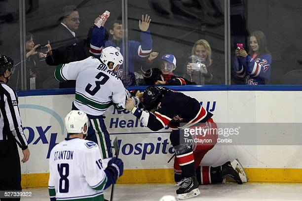 Kevin Bieksa Vancouver Canucks and Brian Boyle New York Rangers fighting at the end of the game as a young fan takes pictures with her phone during...