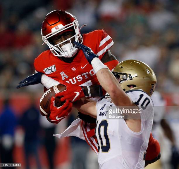 Kevin Brennan of the Navy Midshipmen takes the ball away from Marquez Stevenson of the Houston Cougars for an interception during the fourth quarter...