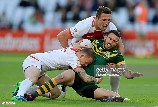 Kevin Brown and Sam Burgess of England tackle Darius Boyd of Australia during the Four Nations match between the England and Australian Kangaroos at...