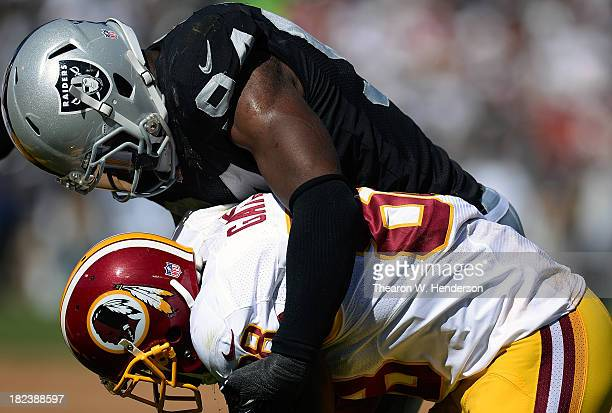 Kevin Burnett of the Oakland Raiders tackles Pierre Garcon of the Washington Redskins during the second quarter at Oco Coliseum on September 29 2013...