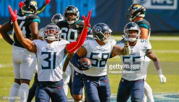 Kevin Byard and Jayon Brown of the Tennessee Titans react after an interception by teammate Harold Landry against the Jacksonville Jaguars during the...