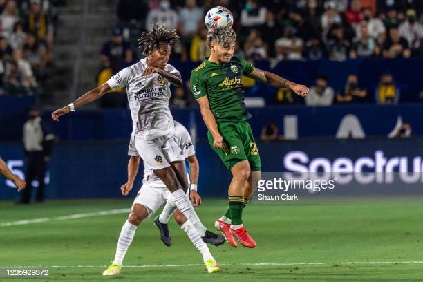 Kevin Cabral of Los Angeles Galaxy competes for a header against Pablo Bonilla of Portland Timbers during the game at the Dignity Health Sports Park...