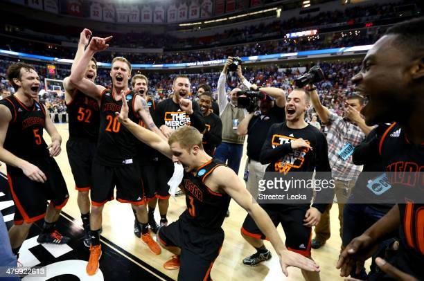 Kevin Canevari of the Mercer Bears celebrates with teammates after defeating the Duke Blue Devils 78-71 during the Second Round of the 2014 NCAA...