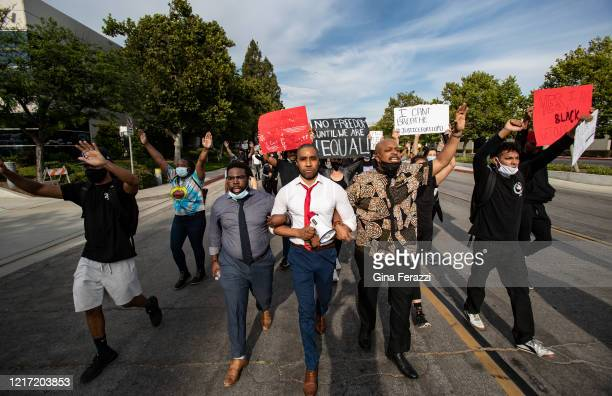 Kevin Carrington, left, Pastor Michael Kelly, middle, of Mt Rubidoux Church and Marquis Johns, right, lock arms to lead demonstrators on a march to...