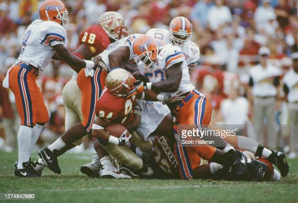 Kevin Carter, Defensive End for the University of Florida Gators tackles and grabs the helmet guard of Rock Preston, Running Back of the Florida...