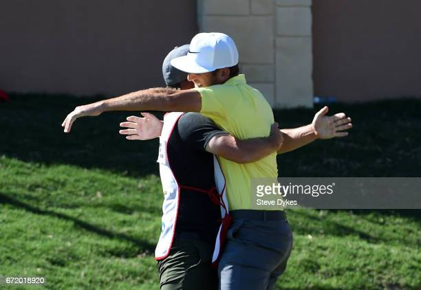 Kevin Chappell celebrates with his caddie Joe Greiner after putting in to win on the 18th green during the final round of the Valero Texas Open at...