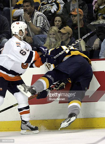 Kevin Colley of the New York Islanders hits Darcy Hordichuk of the Nashville Predators into the boards on January 10 2006 at the Gaylord...