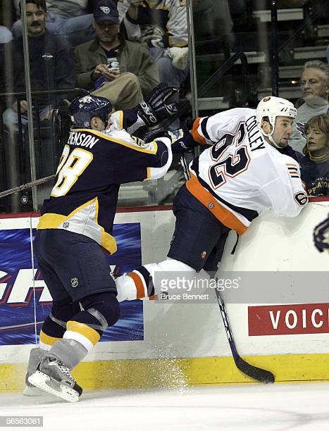 Kevin Colley of the New York Islanders is hit into the boards by Jeremy Stevenson of the Nashville Predators on January 10 2006 at the Gaylord...