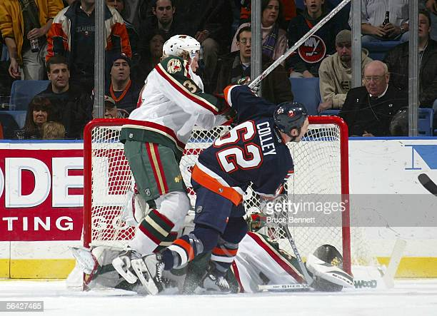 Kevin Colley of the New York Islanders is moved out of the crease by Daniel Tjarnqvist of the Minnesota Wild as goaltender Manny Fernandez scrambles...