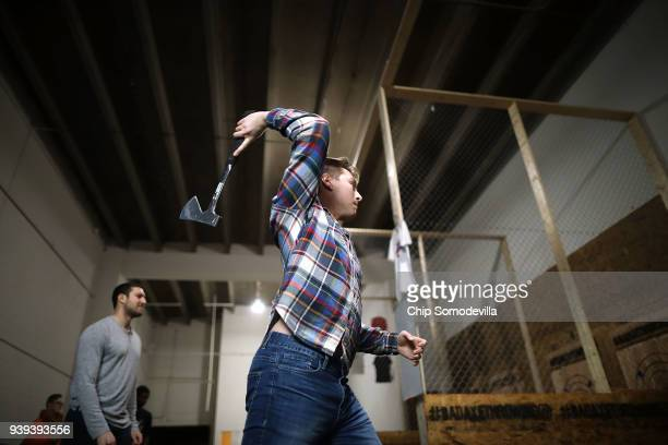 Kevin Conklin throws a hatchet at a wood target wall at Bad Axe Throwing March 28 2018 in Washington DC Conklin and fellow Capitol One employees...