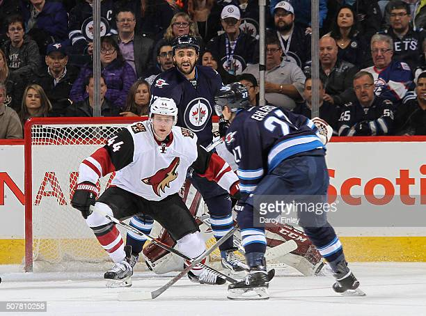 Kevin Connauton of the Arizona Coyotes and Dustin Byfuglien of the Winnipeg Jets watch as Nikolaj Ehlers gets set to take a shot on goal during third...