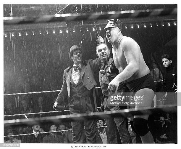 Kevin Conway holding umbrella over fighter in a scene from the film 'Paradise Alley' 1978