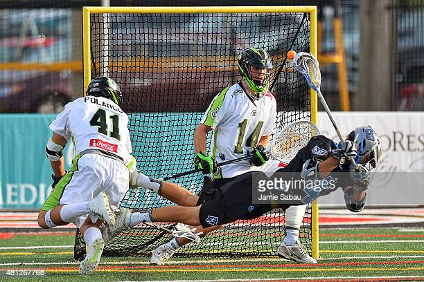 Kevin Cooper of the Ohio Machine scores from behind his back on goalie Drew Adams of the New York Lizards in the first quarter as Nicky Polanco of...