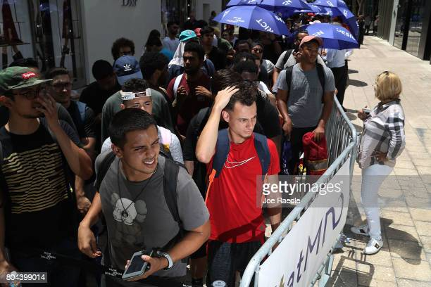 Kevin Cornejo and Daniel Diaz stand in line as people flock to the Louis Vuitton store to purchase limited edition supreme and Louis Vuitton...