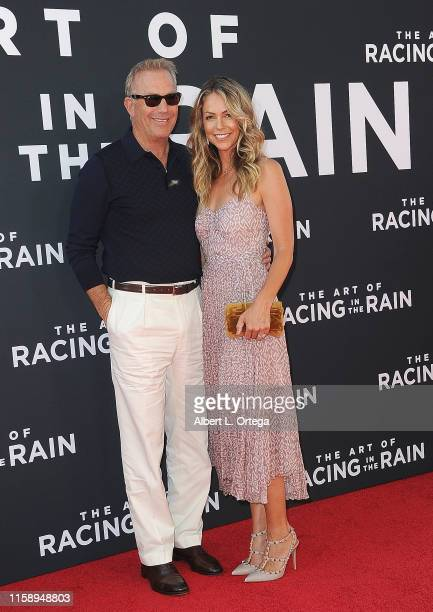 Kevin Costner and Christine Baumgartner arrive for the Premiere Of 20th Century Fox's The Art Of Racing In The Rain held at El Capitan Theatre on...