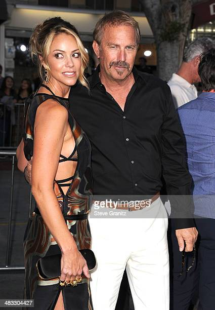 Kevin Costner and Christine Baumgartner arrives at the Draft Day Los Angeles Premiere at Regency Village Theatre on April 7 2014 in Westwood...