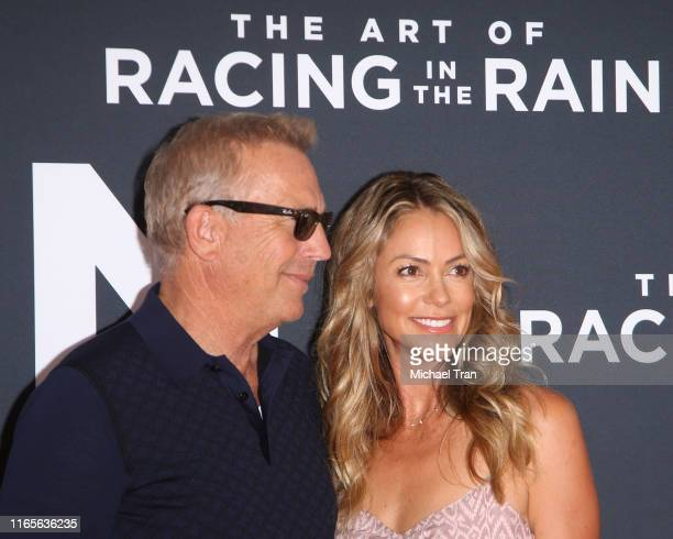 Kevin Costner and Christine Baumgartner attend the Los Angeles premiere of 20th Century Fox's The Art of Racing In The Rain held at El Capitan...