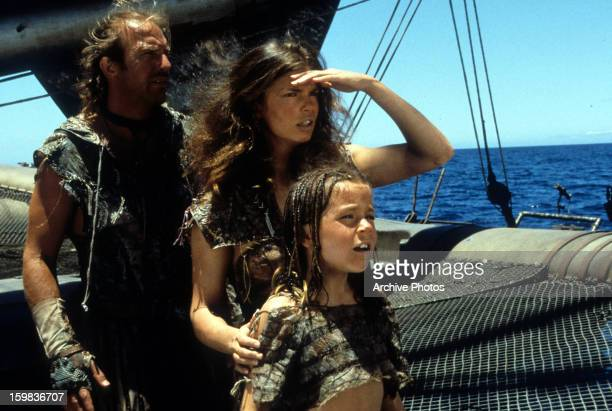 Kevin Costner Jeanne Tripplehorn and Tina Majorino look to the horizon in a scene from the film 'Waterworld' 1995